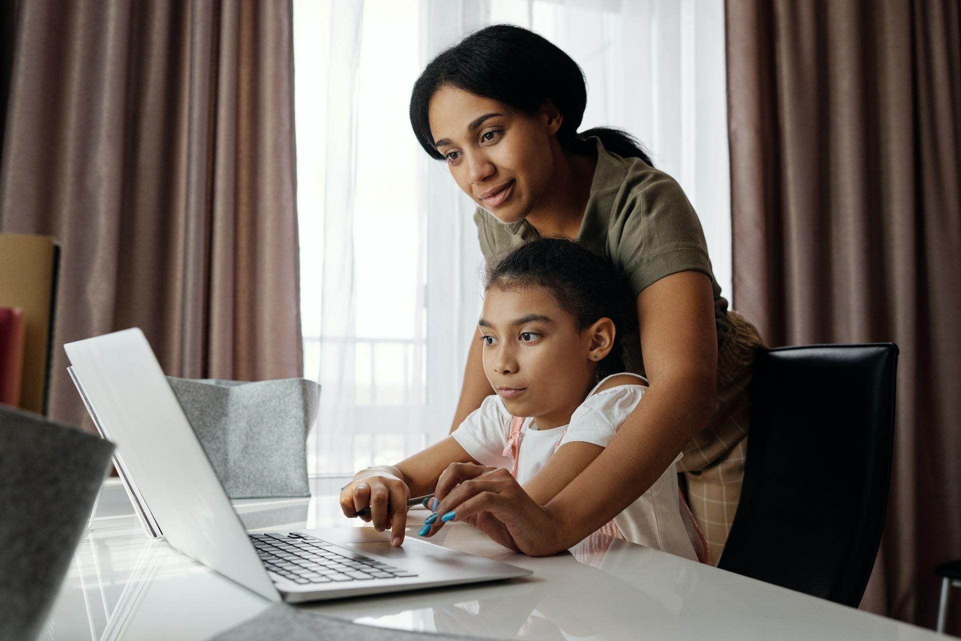 Mom helping girl use computer